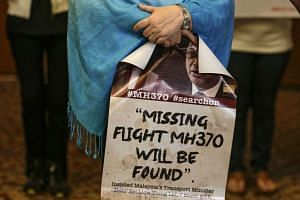 A next of kin of Malaysia Airlines flight MH370 passenger holds a banner at a special press conference in Kuala Lumpur, on 21 July, 2016.