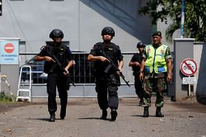 Armed police walk near the gate to the ferry port to the prison island of Nusa Kambangan in Cilacap, Central Java, on July 28, 2016.