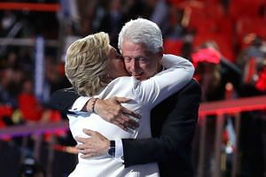 Democratic presidential candidate Hillary Clinton is embraced by her husband, former US President Bill Clinton, at the end of the fourth day of the Democratic National Convention at the Wells Fargo Center, July 28 in Philadelphia, Pennsylvania.