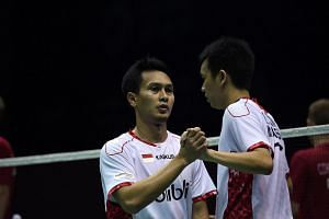 Mohammad Ashan (left) and Hendra Setiawan of Indonesia celebrate their victory against Mads Conrad-Petersen and Pieler Kolding of Denmark during their men's doubles finals group match in the Thomas Cup badminton tournament, on May 22.