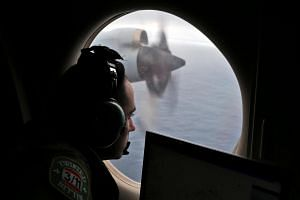 Flight officer Rayan Gharazeddine looks out of a Royal Australian Air Force AP-3C Orion as it flies over the southern Indian Ocean during the search for missing plane on March 22, 2014.