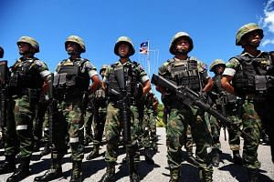 Armed soldiers standing in formation ahead of the constitutional referendum in Thailand's restive southern province of Narathiwat on August 1.