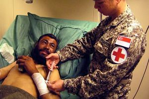 A member of the SAF medical team administering treatment in Afghanistan in 2009. The team slated for Iraq will treat soldiers and civilians.