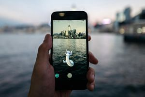 The Dratini character of Nintendo Pokemon Go augmented-reality game, developed by Niantic, is seen in front of the Victoria Harbor on a smartphone in an arranged photograph in Hong Kong, China, on July 25.