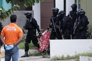 Indonesian anti-terror police with a bag containing a suspected firearm and other evidence taken from a building during yesterday's raid in Batam, where six members of the militant cell were arrested. Singapore's security agencies and their Indonesia