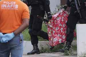 Indonesian anti-terror police carry a bag containing a suspected firearm and other evidence from a building during a raid in Batam, Riau Islands, Indonesia, August 5.