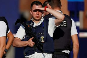 Belgian police officers stand guard outside the main police station after the attack.