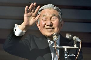 Japanese Emperor Akihito waving to well-wishers gathered for the annual New Year's greetings at the Imperial Palace in Tokyo on Jan 2, 2016.