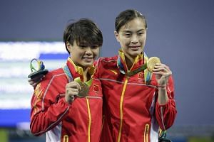 Wu Minxia (right) and Shi Tingmao with their gold medals from the Rio  Olympics women's synchronised 3m springboard at the Maria Lenk Aquatics Centre on August 7.