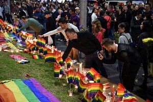 People gather at a vigil in solidarity for the victims of the Orlando nightclub mass shooting at Taylor Square in Sydney, Australia, June 13.