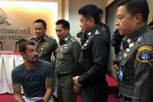 Mr Xavier Andre Justo (seated), a Swiss IT executive appears before the media after being arrested in Thailand for allegedly leaking information about PetroSaudi International.