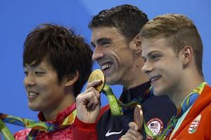 Michael Phelps on the podium with Japan's Masato Sakai (left) and Hungary's Tamas Kenderesi after winning the men's 200m butterfly.