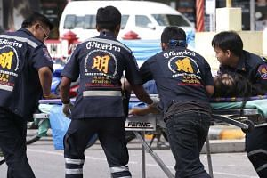Thai rescue workers rush an injured victim to a hospital after two bombs exploded at the city clock tower in Hua Hin, Thailand, on Aug 12, 2016.