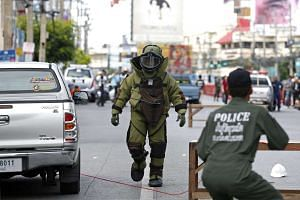 A member of the Explosive Ordnance Disposal walks after defusing a suspicious object after two bombs exploded at the clock tower site in Hua Hin city, Thailand, on Aug 12, 2016.