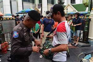 A Thai policeman searching a visitor's bag yesterday at the Erawan Shrine in Bangkok as the authorities increase security following a string of bomb attacks in Phuket and other southern provinces last week. A mobile phone used to trigger an explosion