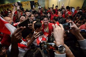 Joseph Schooling poses for photographs with fans at Changi Airport.