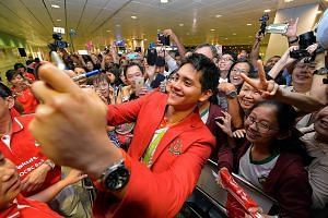 Schooling taking a photo with a crowd of supporters yesterday at Changi Airport's Terminal 3, where some had been waiting since 10pm the previous night. On an emotional and event-filled day for the swimmer, it was also announced that his NS will be d