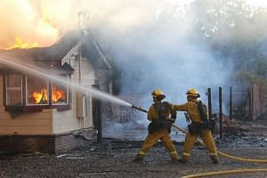 Members of the California Department of Forestry and Fire Protection (Cal Fire) suppressing a fire in a burning structure in Lake County, on August 14, 2016.