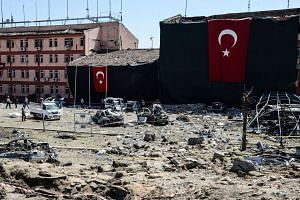 Turkish rescue workers and police inspect the blast scene following a car bomb attack on a police station in the eastern Turkish city of Elazig, on Aug 18, 2016.