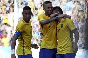 Neymar and Felipe Anderson of Brazil celebrate with teammate Luan (centre) after Luan scored the team's fifth goal of the game.