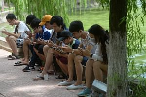 People playing Pokemon Go at a public park next to Hoan Kiem Lake in the centre of Hanoi on August 10.