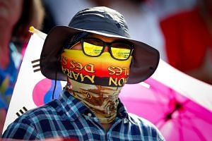 A spectator protects his face from the midday sun at the Olympic Games in Rio  on  Aug 6, 2016.