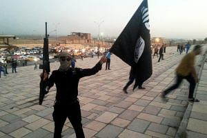 A fighter of the Islamic State of Iraq and the Levant (ISIL) holds an ISIL flag and a weapon on a street in the city of Mosul in 2014.