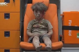 One of the children rescued from rubble in the video released by Syria's Aleppo Media Centre. Warplanes from the Assad regime pounded rebel-held districts in Aleppo on Wednesday, while rebel shelling in the regime- controlled west killed 12 people.