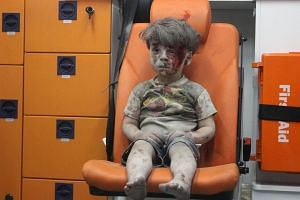 Omran, a four-year-old Syrian boy covered in dust and blood, sits in an ambulance after being rescued from the rubble of a building hit by an air strike.