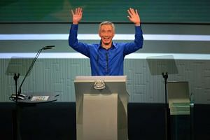 Prime Minister Lee Hsien Loong waving to the audience after returning to finish his speech.
