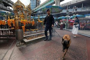 A policeman inspecting the area around the Erawan Shrine in Bangkok last Wednesday, the first anniversary of the bombing of the shrine. Even as two suspects stand trial for the assault, more than a dozen others remain at large and a convincing motive