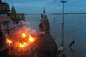 Indian mourners perform a cremation on the roof of a building the Manikarnika Ghat in Varanasi on Aug 23, 2016.