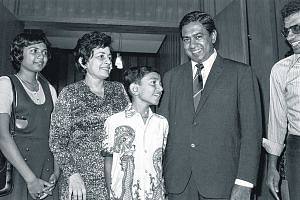 Mr S R Nathan being greeted by his wife and children upon his safe return at the Singapore airport.