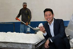 Mr Cheng with the rock sugar that his company manufactures. In the background, a worker is transferring rock sugar to a machine, which smashes the sugar into smaller pieces. Mr Cheng says the company plans to redevelop its site to capitalise on the s