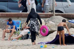 A woman wears a burkini, a swimsuit that leaves only the face, hands and feet exposed, on a beach in Marseille, France on Aug 17, 2016.