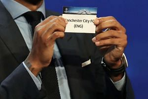 French ex-football player Thierry Henry shows a piece of paper bearing the name of Manchester City during the UEFA Champions League draw in Monaco.