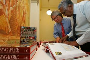 Professor Tommy Koh and Mr S R Nathan looking at Singapore: The Encyclopedia in 2006.