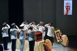 Final salute for Mr Nathan from the coffin bearer party from the armed forces and police during the state funeral service at the University Cultural Centre yesterday.