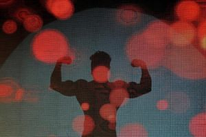 A participant casts his shadow on a screen as he flexes his muscles during a bodybuilding competition.