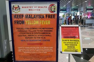 A travel advisory on the yellow fever infection is seen as travelers pass by the automatic passport gate at Kuala Lumpur International Airport at Sepang, outside Kuala Lumpur, Malaysia, Aug 28.