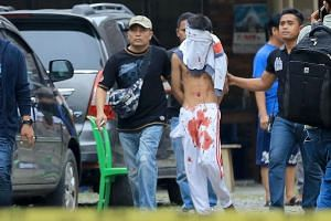 The 17-year-old attacker being escorted by plainclothes policemen in Medan yesterday.