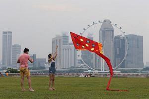 People enjoying outdoor activities at Marina Barrage on Aug 27, 2016, despite hazy conditions.