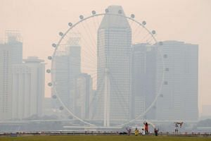 People take photos near the Singapore Flyer observatory wheel shrouded by haze on August 26.