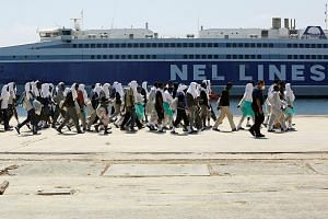 Migrants disembarking from an Italian Navy ship  in the Sicilian harbour of Augusta, Italy on Aug 21, 2016.