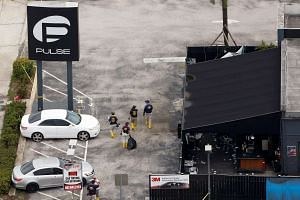 FBI officials walk through the parking lot of the Pulse nightclub in Orlando, days after the shooting on June 12, 2016.