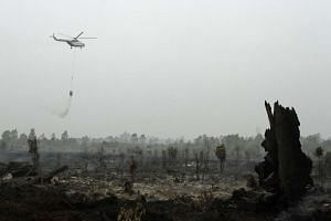 A helicopter from Indonesia's National Disaster Mitigation Agency dousing fires in Kampar in Riau province on Monday. Several areas in Riau were hit by severe air pollution in recent days, prompting some schools to suspend classes since Monday.