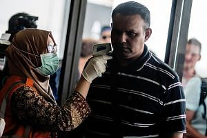 An airport health official checking the temperature of passengers from Singapore at Yogyakarta Airport yesterday.