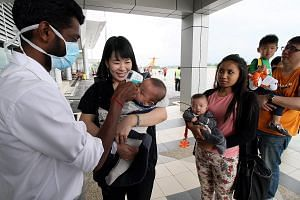 Malaysian health department staff conduct body temperature checks on passengers of a Firefly flight from Singapore at the Sultan Azlan Shah Airport in Ipoh, as part of precautionary measures to screen for the Zika virus.
