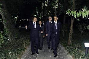Mr Xi and Mr Obama on a stroll around the West Lake State Guesthouse. Mr Xi urged the US to play a