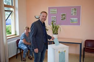 AfD candidate Leif-Erik Holm casting his vote in the Mecklenburg- Western Pomerania state election in Klein Trebbow yesterday. Opinion polls show that Dr Merkel's CDU may be pipped even from second place at the polls.